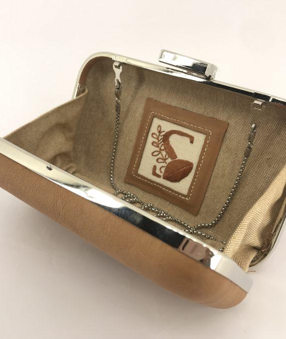 Clutch handmade em couro com o logotipo da marca bordada manualmente a seda natural.